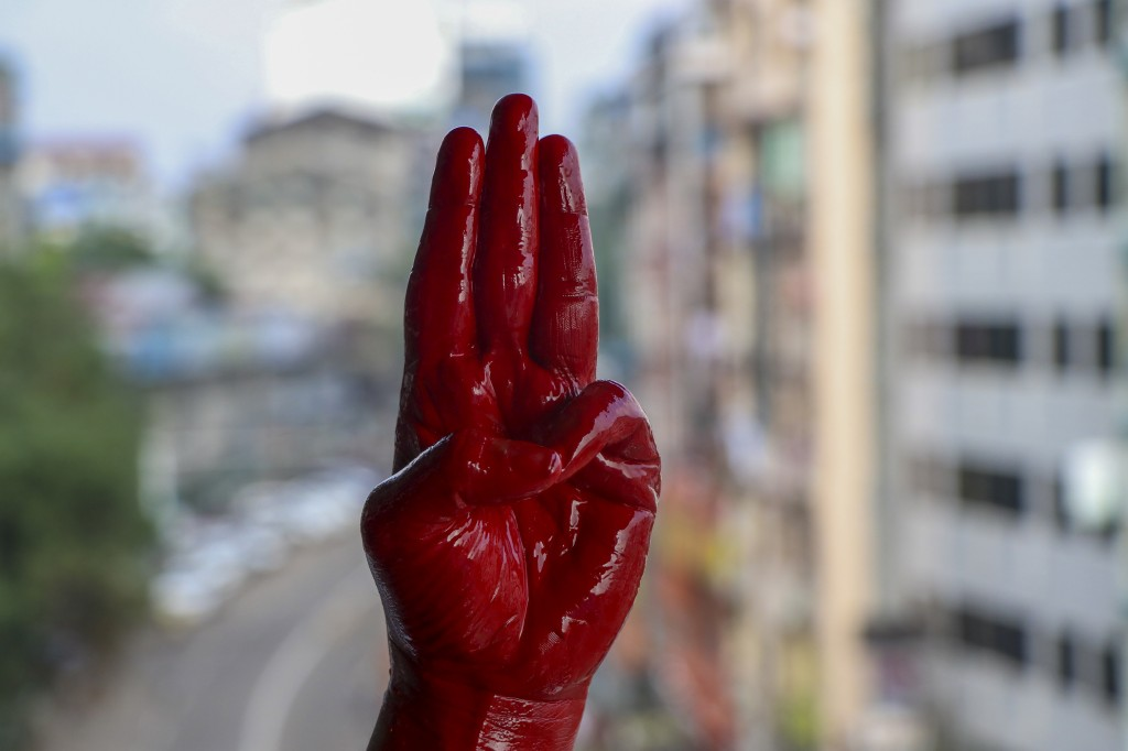 Anti-coup protester shows three-fingered salute of resistance, his hand covered in red paint.