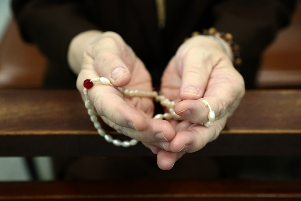Sister Mary Carol Kardell, of the Felician Sisters of North America, prays with rosary beads during morning Mass at St. Anne Home in Greensburg, Pa., ...