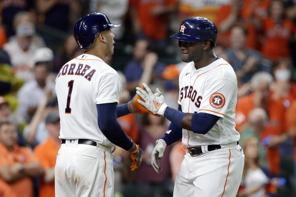 Houston Astros' Carlos Correa (1) and Yordan Alvarez, right, celebrate Alvarez's home run against the Oakland Athletics during the sixth inning of a b...
