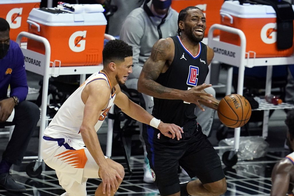 Los Angeles Clippers forward Kawhi Leonard, right, is defended by Phoenix Suns guard Devin Booker during the first half of an NBA basketball game Thur...