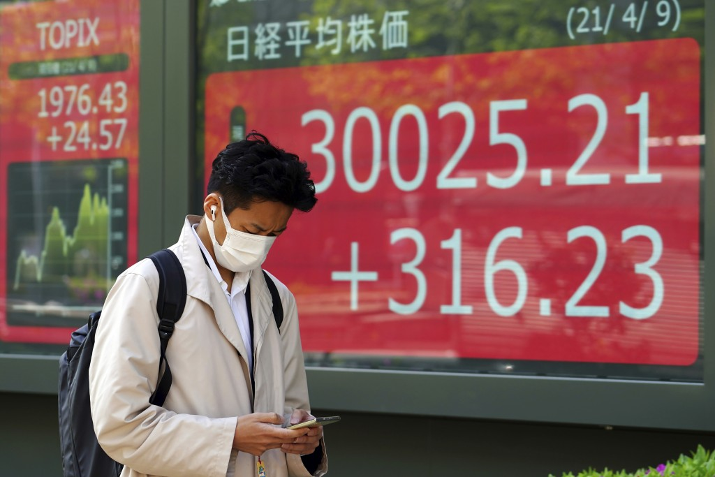 A man wearing a protective mask walks in front of an electronic stock board showing Japan's Nikkei 225 index at a securities firm in Tokyo Friday, Apr...
