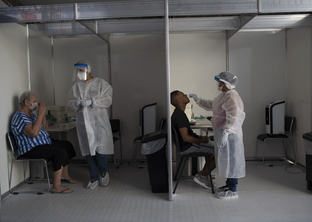 People get nasal swabs taken for COVID-19 tests in the Mare Complex favela of Rio de Janeiro, Brazil, Thursday, April 8, 2021. Nations around the worl...