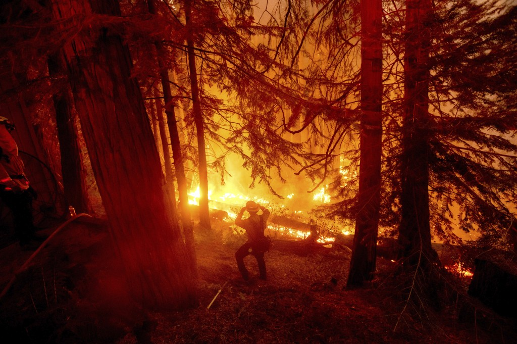 FILE - In this Sept. 7, 2020, file photo, a firefighter battles the Creek Fire in the Shaver Lake community of Fresno County, Calif. California will a...