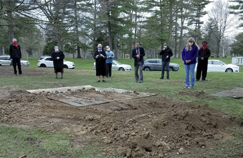 In this April 24, 2020, photo provided by Sister Mary Alfonsa Van Overberghe, nuns from a convent in Livonia, and others gather at the burial site of ...