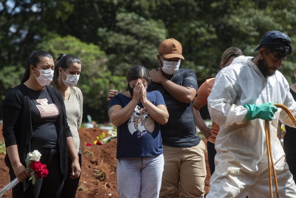 FILE - In this April 7, 2021, file photo, people attend the burial of a relative who died from complications related to COVID-19 at the Vila Formosa c...