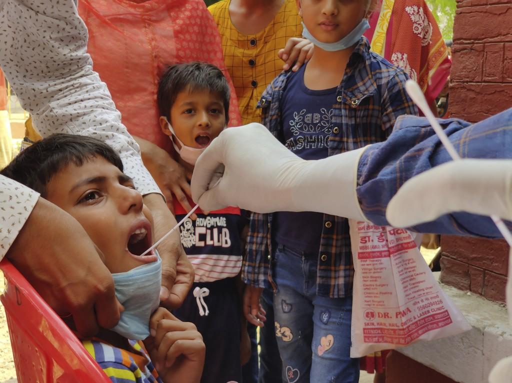 一名醫療人員4月8日在印度安拉阿巴德(Prayagraj)為一名孩童進行採檢。(美聯社圖片)