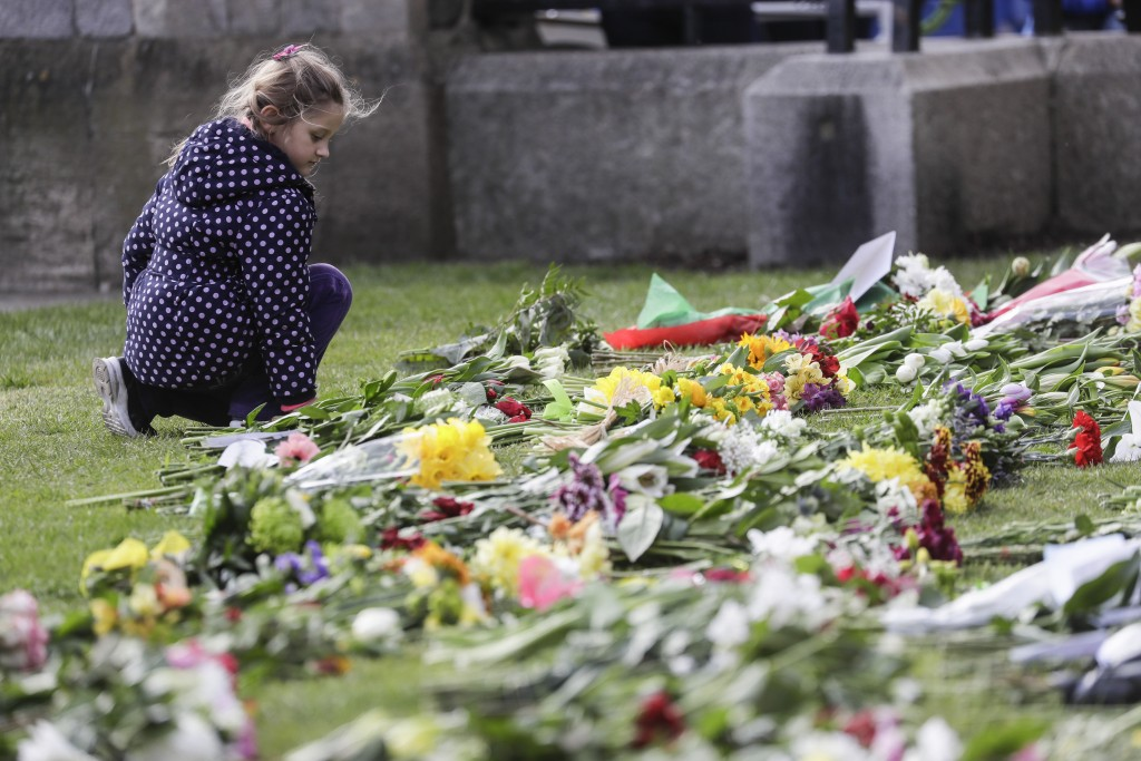 A child looks at flowers outside of Windsor Castle in Windsor, England after the announcement regarding the death of Britain's Prince Philip, Friday, ...