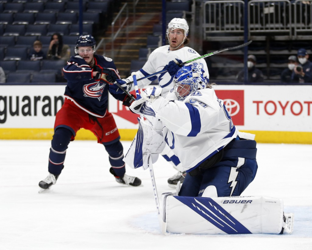 Tampa Bay Lightning goalie Andrei Vasilevskiy, right, stops a shot in front of Columbus Blue Jackets forward Eric Robinson, left, and Lightning defens...