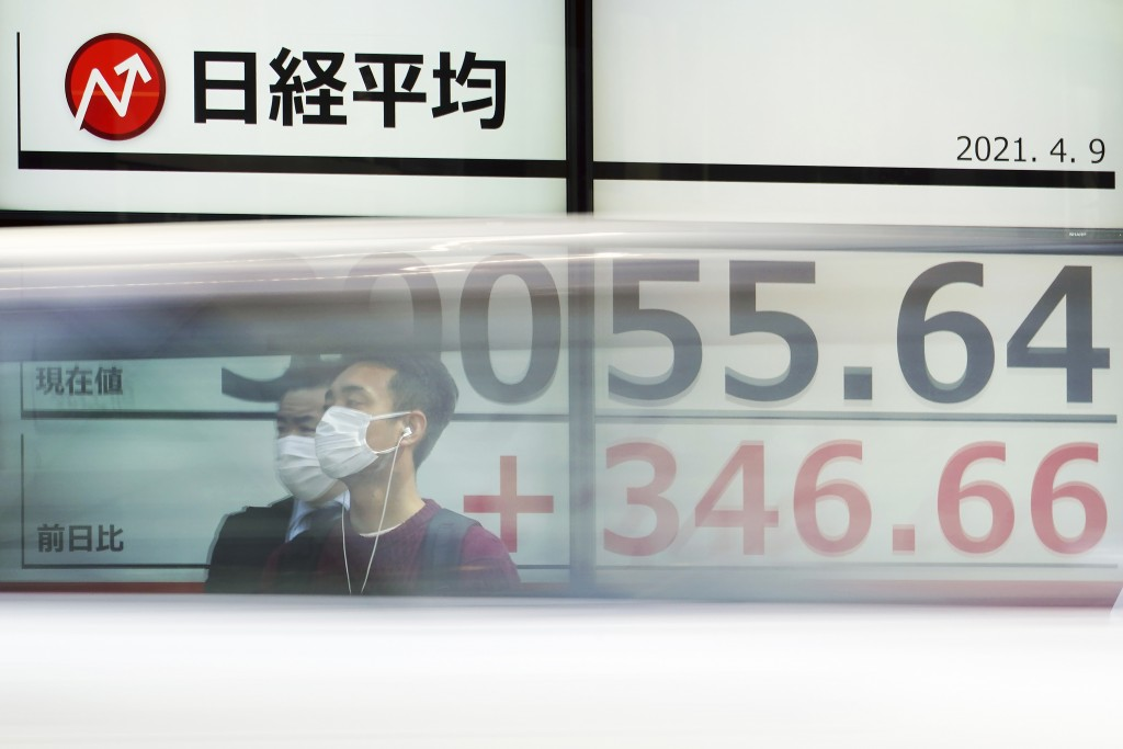 Men wearing protective masks stand in front of an electronic stock board showing Japan's Nikkei 225 index at a securities firm as a car passes by in T...
