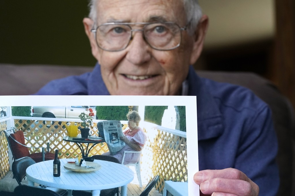 """Victor Hamilton displays a photo of his late wife, Nancy """"Nicki"""" Hamilton, who died about a year earlier after contracting COVID-19 at a choir practic..."""