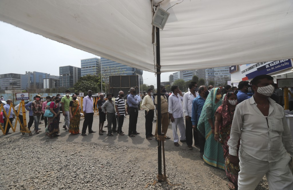 People queue up for COVID-19 vaccine in Mumbai, India, Thursday, April 8, 2021. Nations around the world set new records Thursday for COVID-19 deaths ...