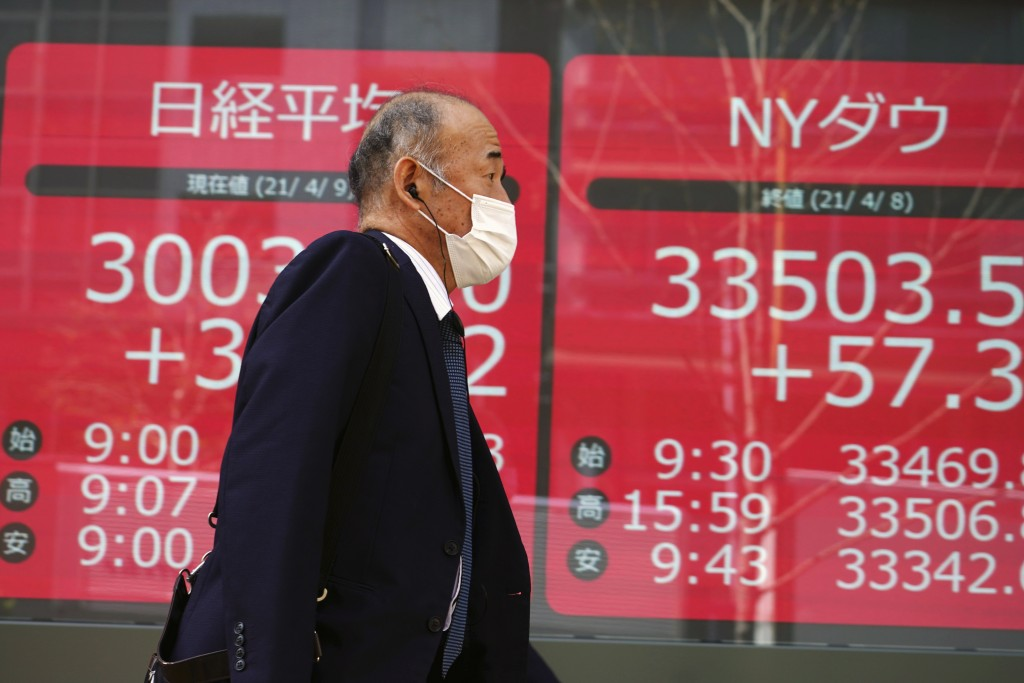 A man wearing a protective mask walks in front of an electronic stock board showing Japan's Nikkei 225 and New York Dow indexes at a securities firm i...