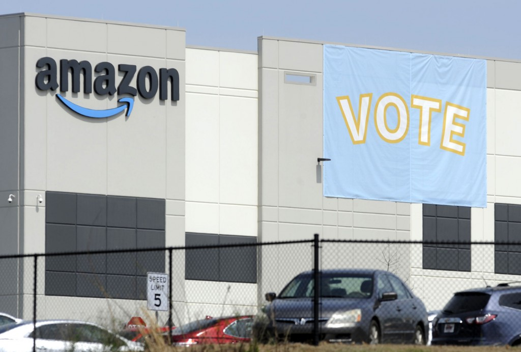 FILE - In this Tuesday, March 30, 2021 file photo, a banner encouraging workers to vote in labor balloting is shown at an Amazon warehouse in Bessemer...