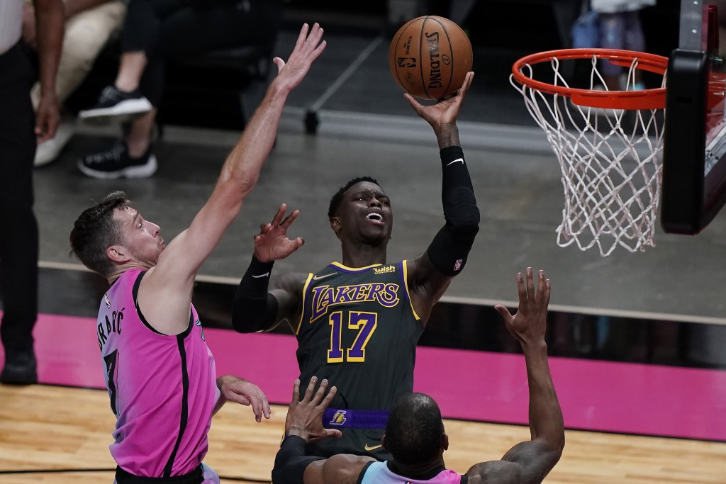 Los Angeles Lakers guard Dennis Schroder (17) drives to the basket as Miami Heat guard Goran Dragic (7) defends, during the first half of an NBA baske...