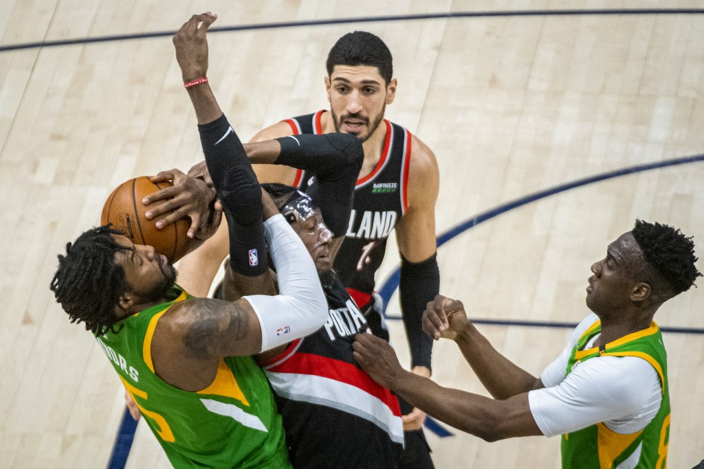 Portland Trail Blazers forward Robert Covington, center, and Utah Jazz center Derrick Favors, left, compete for possession of the ball during the firs...