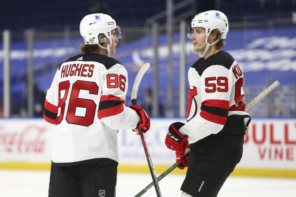 New Jersey Devils forward Jack Hughes (86) celebrates his goal with forward Janne Kuokkanen (59) during the first period of the team's NHL hockey game...
