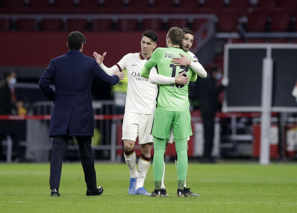 Roma's head coach Paulo Fonseca, left, celebrates with players at the end of the Europa League first leg quarterfinal soccer match between Ajax and Ro...
