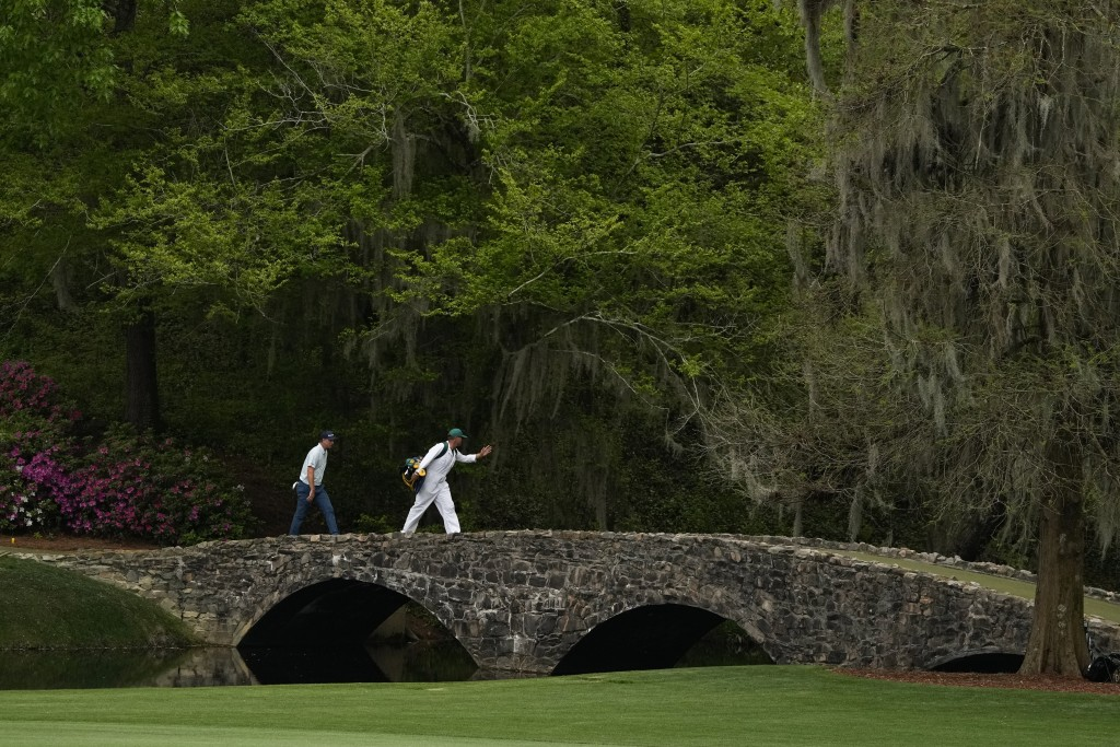 Justin Rose, of England, crosses the Hogan Bridget with his caddie David Clark during the first round of the Masters golf tournament on Thursday, Apri...