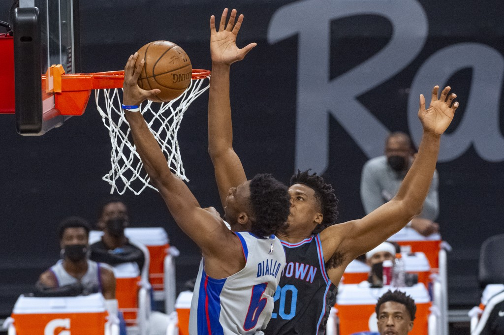 Detroit Pistons guard Hamidou Diallo (6) lays the ball up over Sacramento Kings center Hassan Whiteside (20) during the first quarter of an NBA basket...