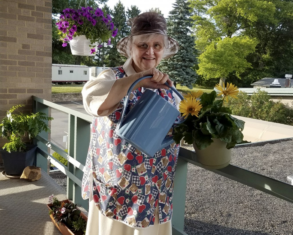 In this photo provided by Sister Mary Jeanine Morozowich, Felician Sister Mary Evelyn Labik waters flowers at St. Anne Home in Greensburg, Pa., on Jun...