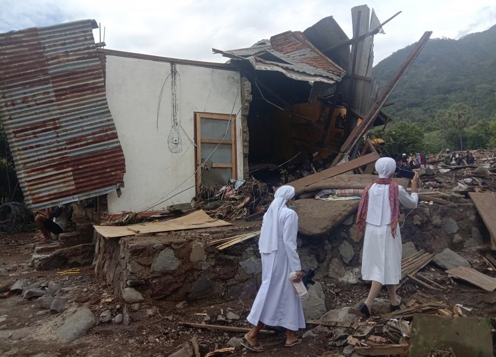 Nuns walk past a damaged house at a flood-affected village in Ile Ape on Lembata Island, East Nusa Tenggara province, Indonesia, Tuesday, April 6, 202...