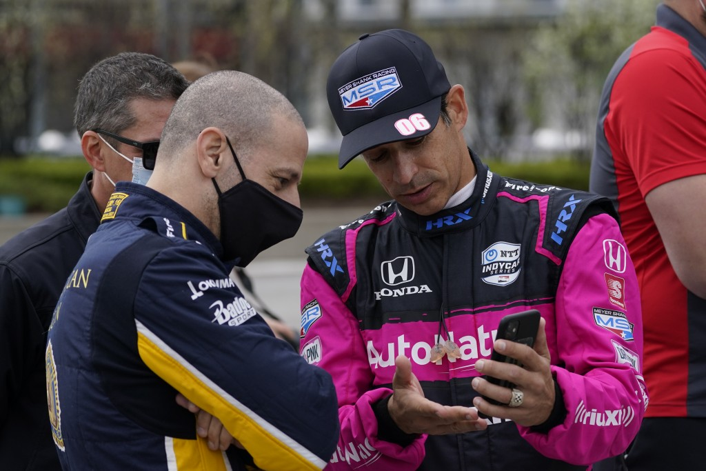 Tony Kanaan, of Brazil, left foreground, talks with Helio Castroneves, of Brazil, before testing at the Indianapolis Motor Speedway, Thursday, April 8...
