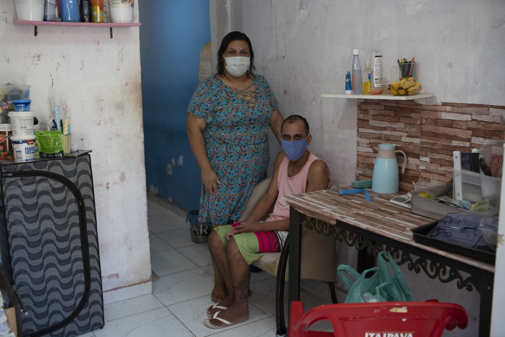 Rachel de Lima Ribeiro, who recovered from COVID-19, poses for a photo with her handicapped husband Felipe da Silva inside their small home in the Mar...