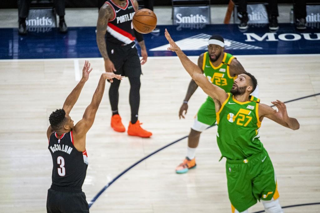 Portland Trail Blazers guard CJ McCollum (3) shoots over Utah Jazz center Rudy Gobert (27) during the first half of an NBA basketball game Thursday, A...