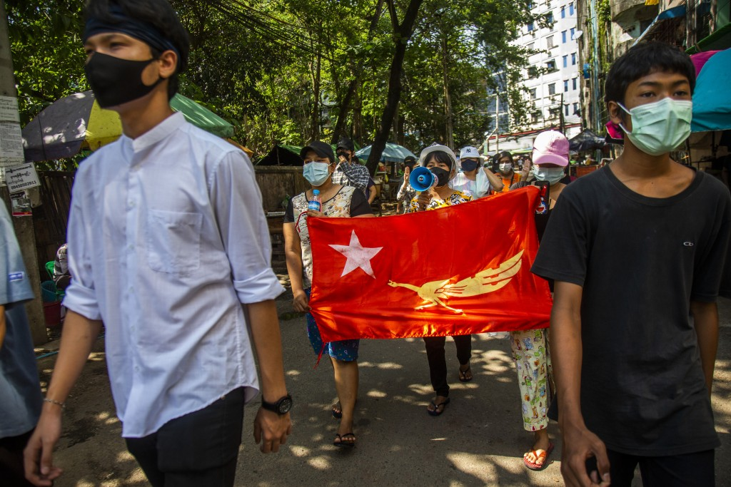 Protesters chant slogans and march in the street of Myaynigone township during the anti-coup demonstration in Yangon, Myanmar, Friday, April 9, 2021. ...