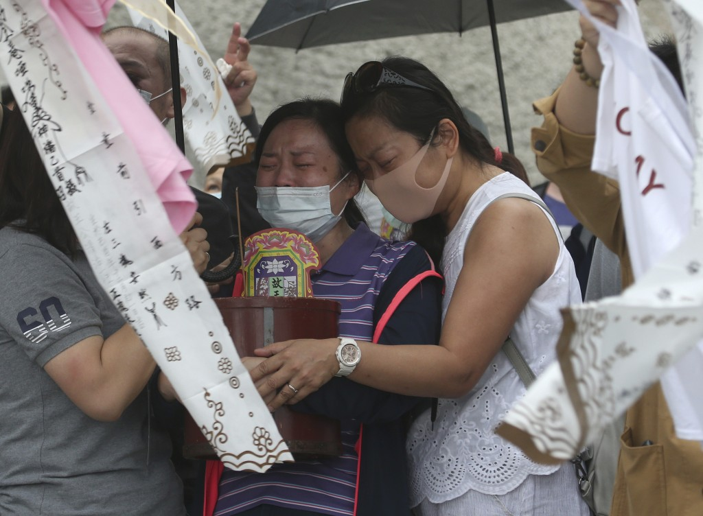 The families of the victims in a train crash try to conjure their spirits near Taroko Gorge in Hualien, Taiwan on Saturday, April 3, 2021. The train p...