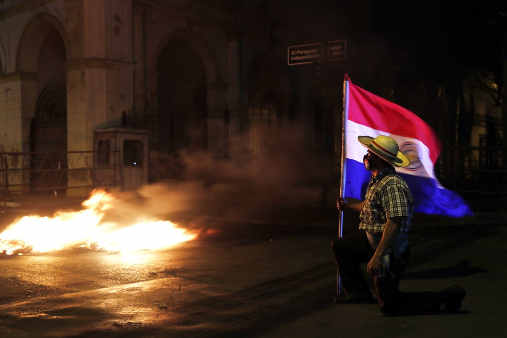 A man carries a national flag during a protest in front of the Congress building, asking for the resignation of President Mario Abdo Benitez over his ...
