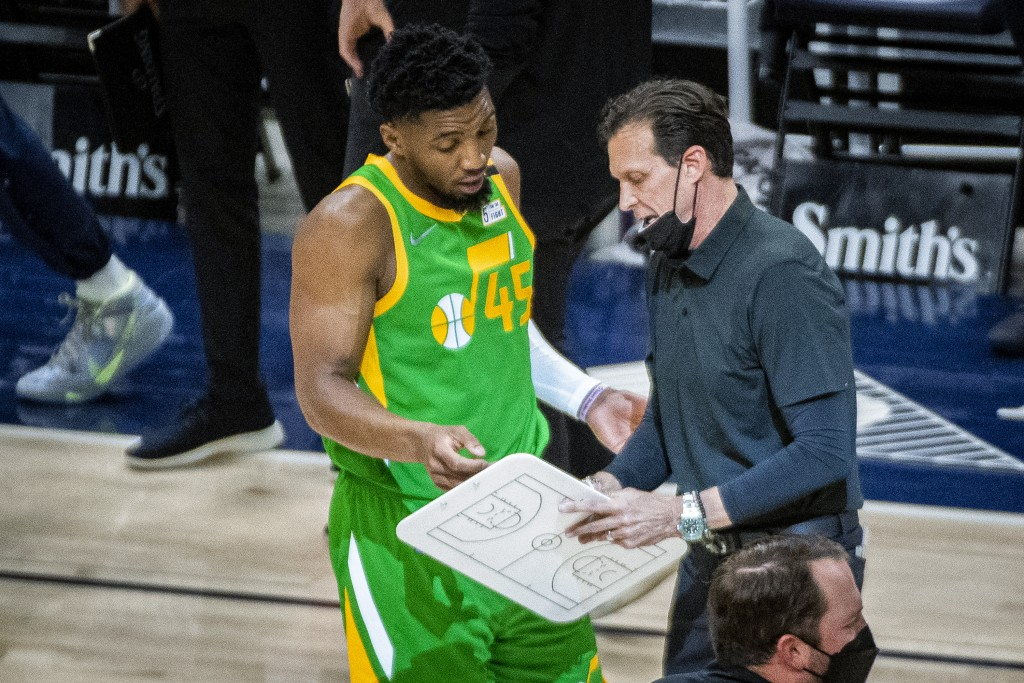 Utah Jazz guard Donovan Mitchell (45) talks with coach Quin Snyder during a timeout in the first half of the team's NBA basketball game against the Po...