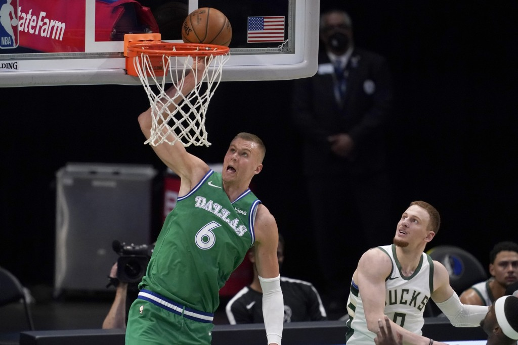 Dallas Mavericks center Kristaps Porzingis (6) attempts to dunk as Milwaukee Bucks guard Donte DiVincenzo (0) looks on in the first half of an NBA bas...