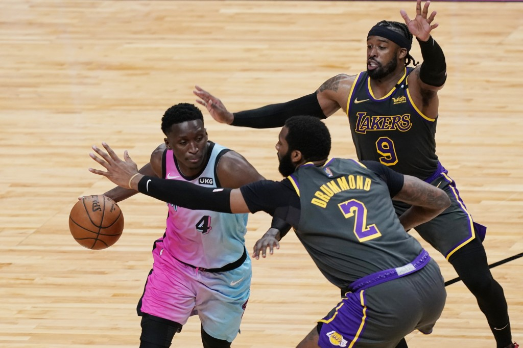 Los Angeles Lakers guard Wesley Matthews (9) and center Andre Drummond (2) defend Miami Heat guard Victor Oladipo (4), during the second half of an NB...