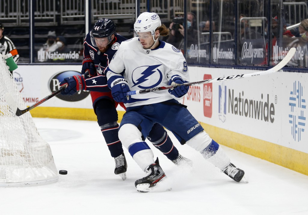 Tampa Bay Lightning defenseman Mikhail Sergachev, right, chases the puck in front of Columbus Blue Jackets defenseman Vladislav Gavrikov during the fi...