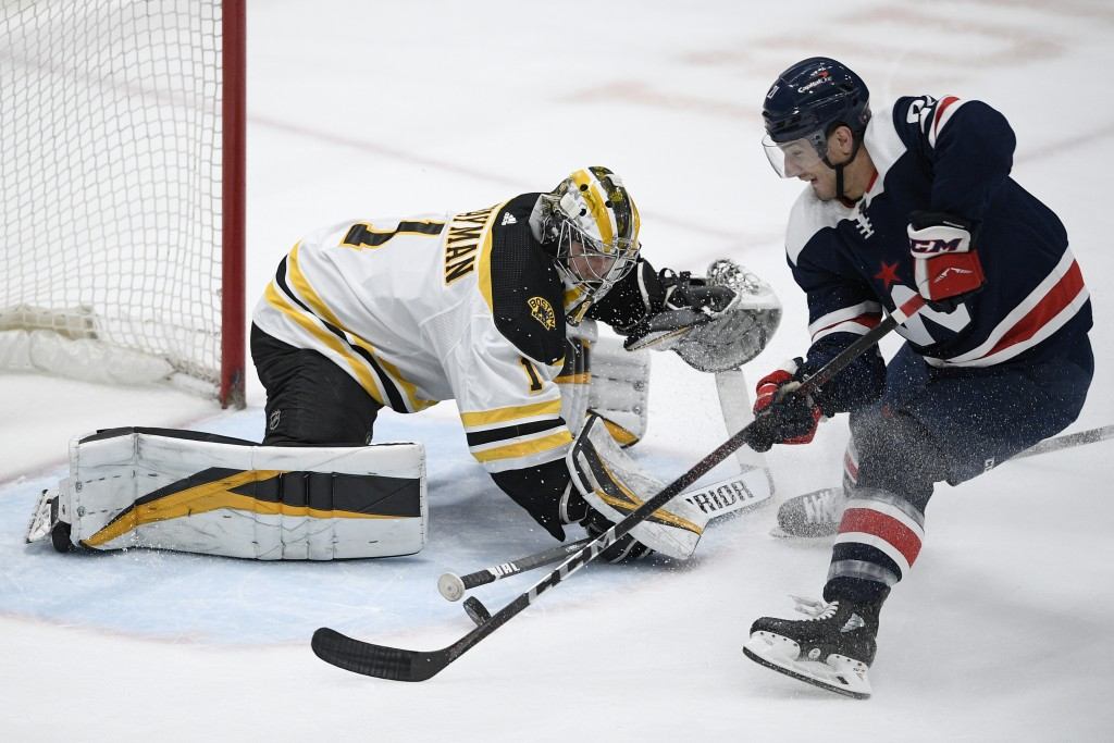 Boston Bruins goaltender Jeremy Swayman (1) defends against Washington Capitals right wing Garnet Hathaway, right, during the first period of an NHL h...