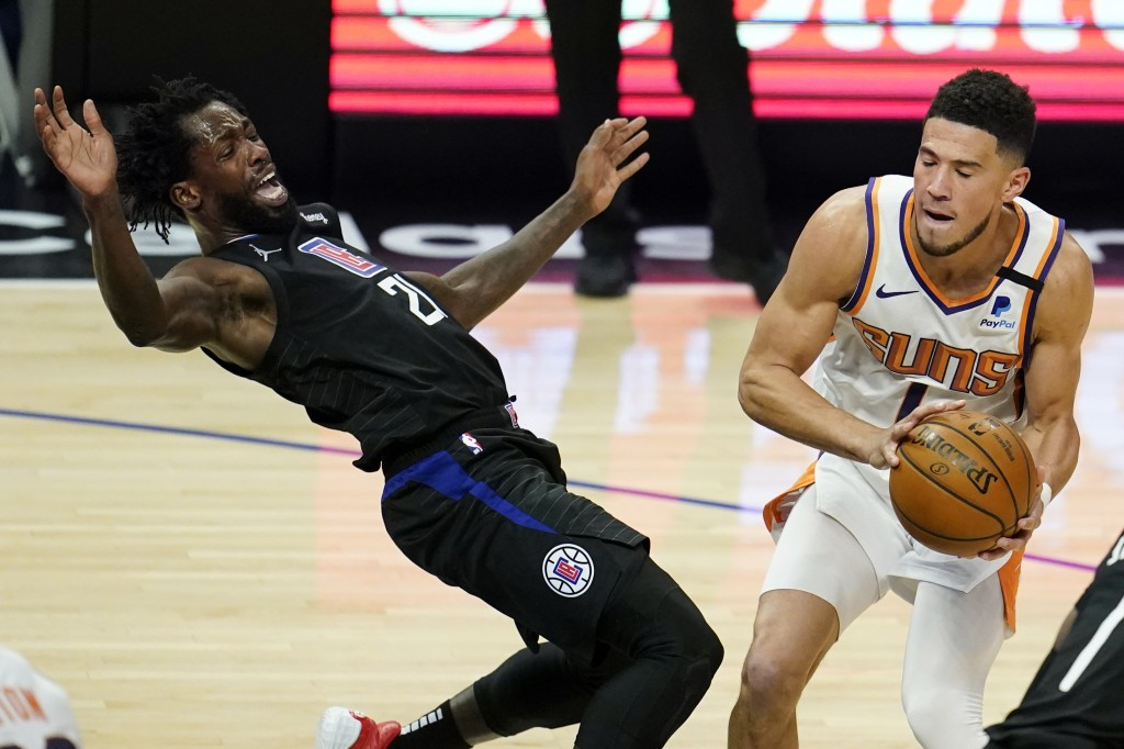 Los Angeles Clippers guard Patrick Beverley, left, falls back while defending on Phoenix Suns guard Devin Booker during the first half of an NBA baske...