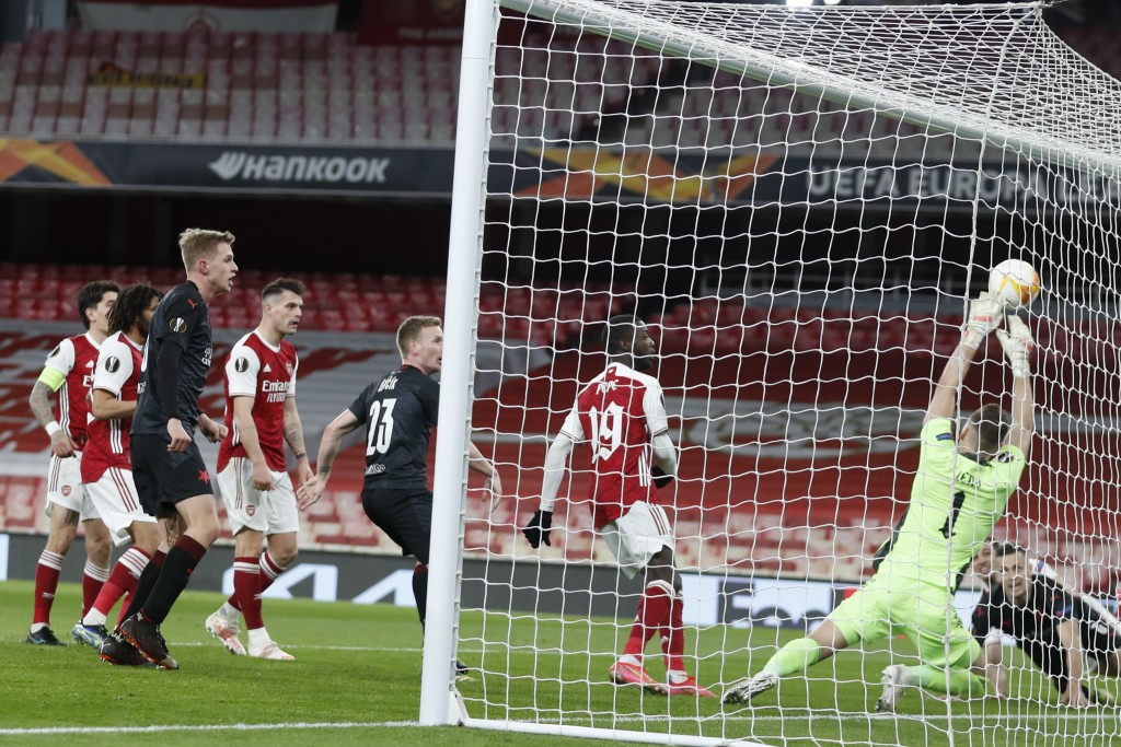 Slavia Prague's Tomas Holes, bottom right, scores his side's first goal during the Europa League quarterfinal soccer match between Arsenal and Slavia ...