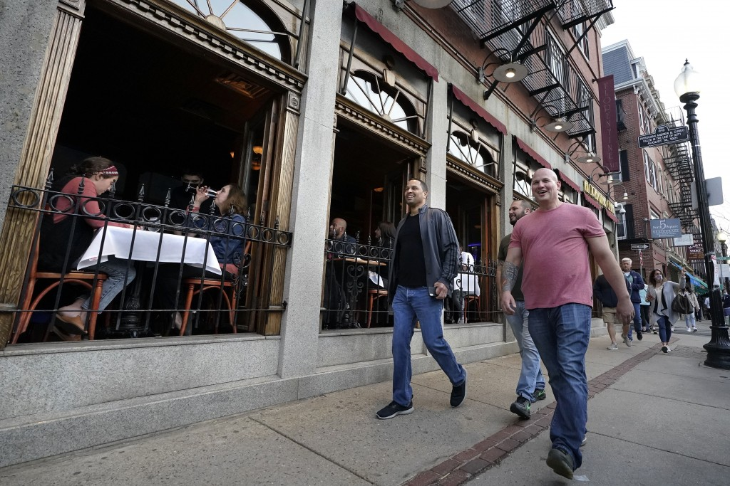 FILE - In this March 25, 2021, file photo, people, right, walk past diners seated near open windows, left, in a restaurant on a busy street in the his...