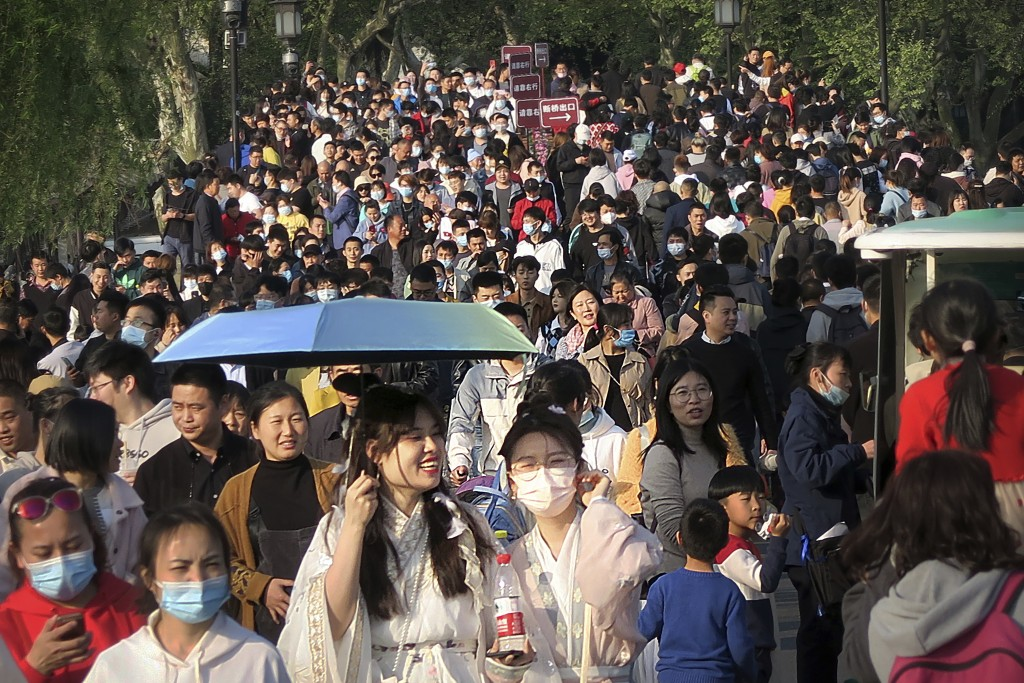 Visitors wearing face masks to protect against COVID-19 walk across a causeway at the West Lake in Hangzhou in eastern China's Zhejiang Province, Sund...