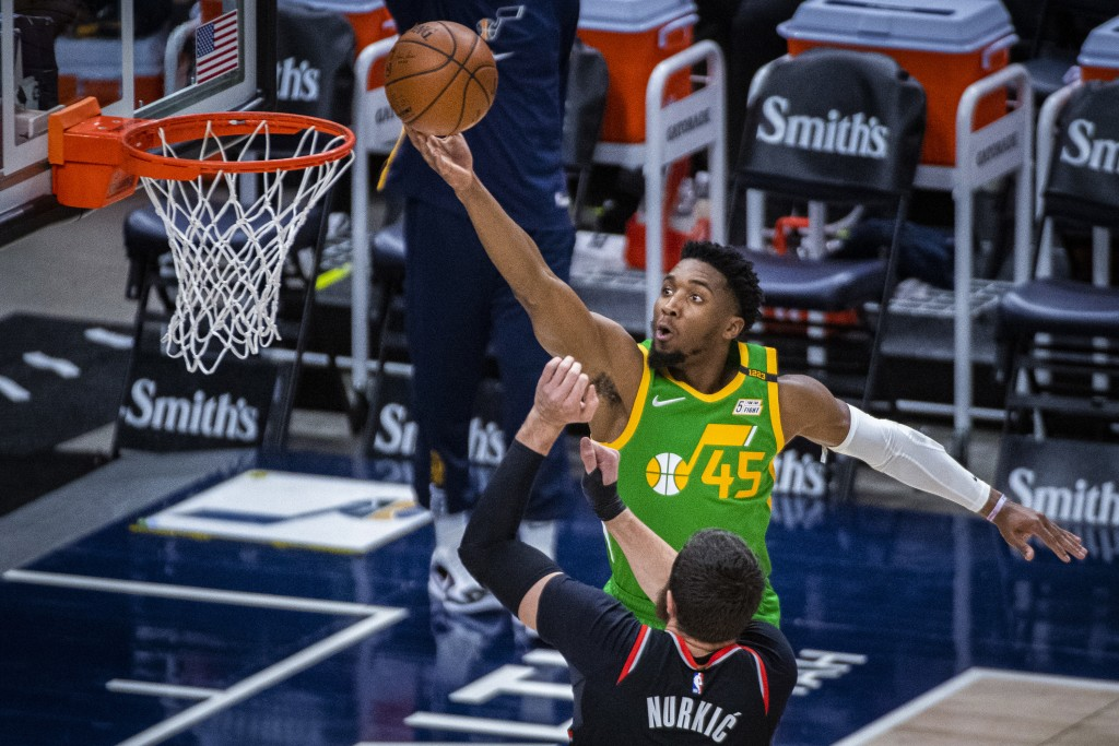 Utah Jazz guard Donovan Mitchell (45) lays the ball up while guarded by Portland Trail Blazers center Jusuf Nurkic (27) during the first half of an NB...