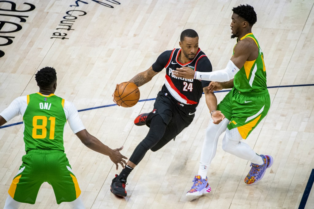 Portland Trail Blazers forward Norman Powell (24) drives the ball on Utah Jazz guard Donovan Mitchell, right, during the first half of an NBA basketba...