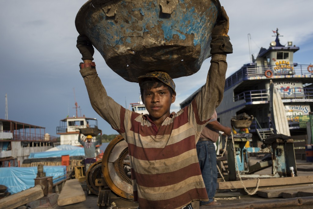 Michael Urquilla carries scrap metals for recycling to a cargo ship, at the Masusa port in Iquitos, Peru, Friday, March 19, 2021. It's been almost a y...