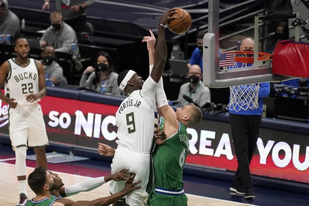 Milwaukee Bucks center Bobby Portis (9) attempts to dunk over Dallas Mavericks center Kristaps Porzingis, right, in the first half of an NBA basketbal...