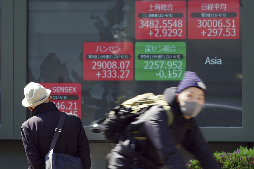 A man looks at an electronic stock board showing Japan's Nikkei 225 and the Asian indexes at a securities firm in Tokyo Friday, April 9, 2021. Shares ...
