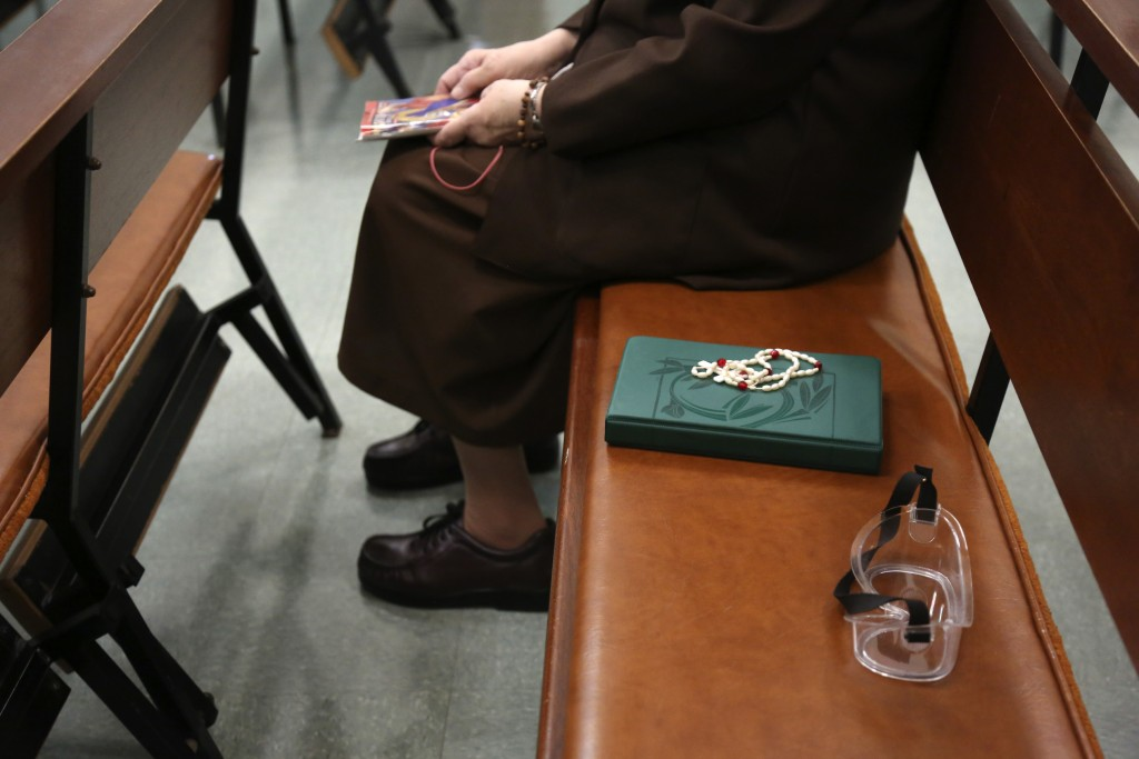 Sister Mary Carol Kardell, of the Felician Sisters of North America, sits beside a Bible, rosary beads and goggles during morning Mass at St. Anne Hom...