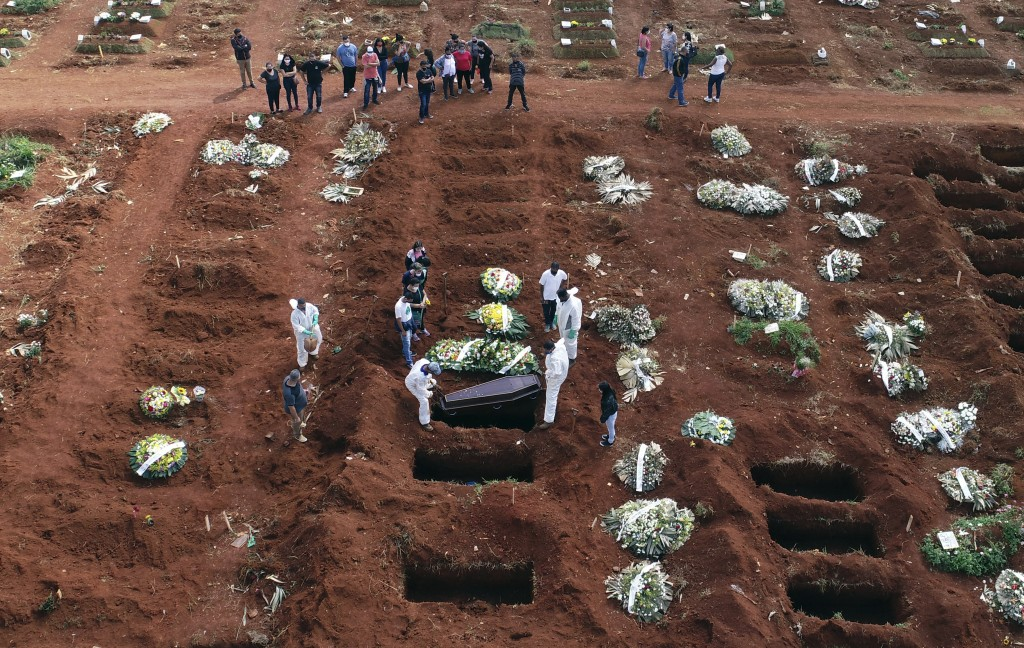 FILE - In this April 7, 2021, file photo, cemetery workers wearing protective gear lower the coffin of a person who died from complications related to...