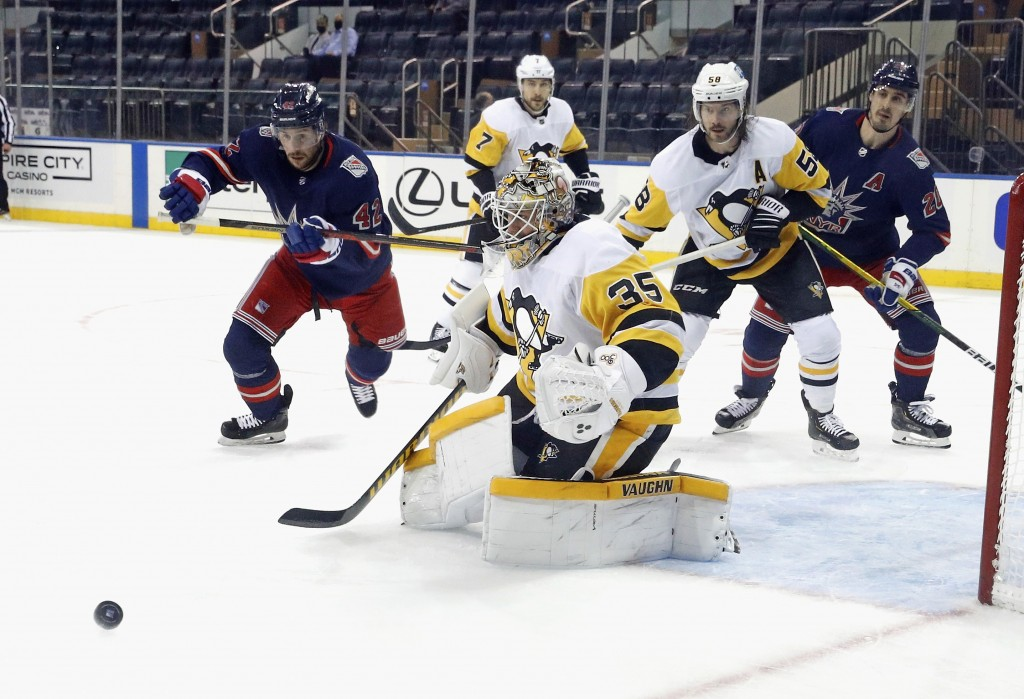 Pittsburgh Penguins' Tristan Jarry (35) sticks aside a  shot as New York Rangers' Brendan Smith (42) looks for the rebound during the first period of ...
