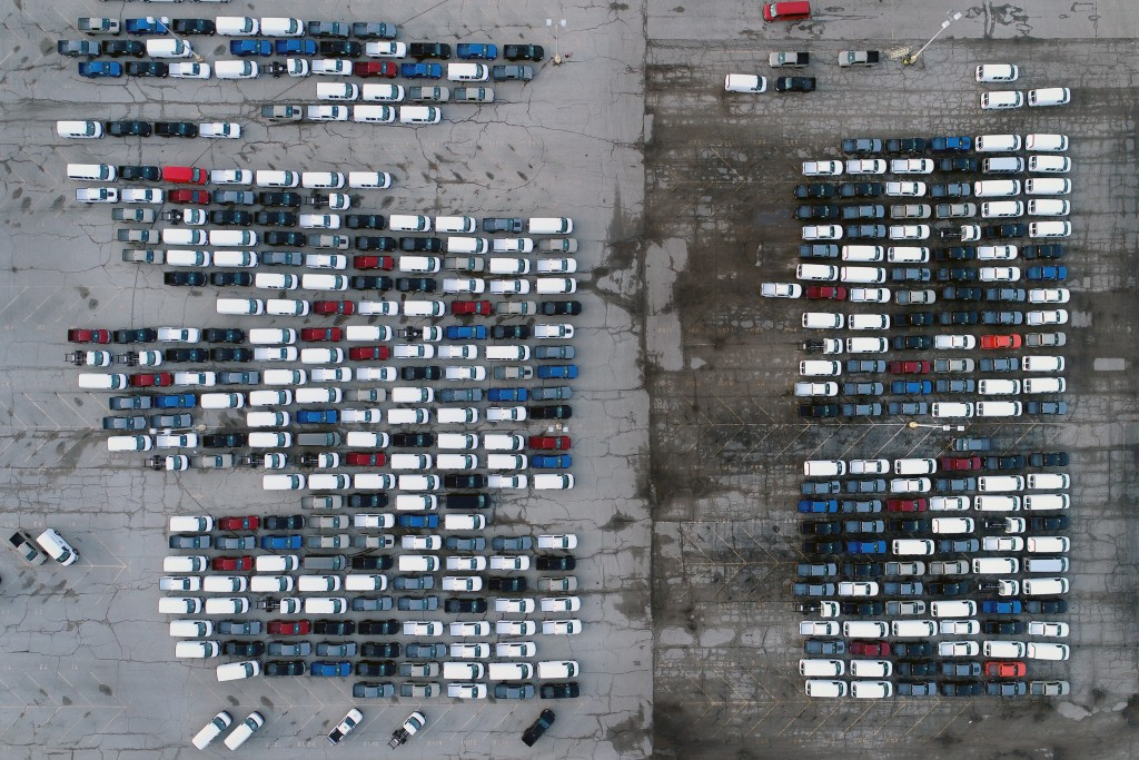In this aerial photo, mid-sized pickup trucks and full-size vans are seen in a parking lot outside a General Motors assembly plant where they are prod...