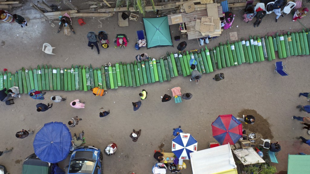 Dozens of empty oxygen cylinders lay across a dirt road, as people wait for a shop to open in order to refill their tanks in the Villa El Salvador nei...